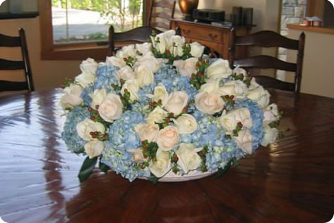 An elegant floral arrangement of white and blue flowers by Bondville Bloomist