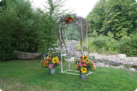 Floral elements incorporated into a wedding arch by a picturesque stream
