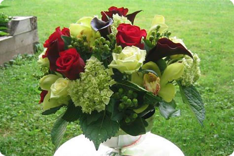 Outdoor floral arrangement in a vase, highlighted by deep red roses